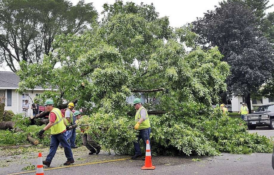 Workers try to clear a tree blocking the southbound lane of the 1000-block of 25th Avenue North Friday, June 21, 2013 in St. Cloud, Minn. after heavy winds caused widespread damage and power outages to as many as an estimated 20,000 customers. (AP Photo/St. Cloud Times, Kimm Anderson) Photo: Kimm Anderson, Associated Press