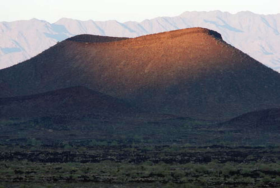 El Pinacate is a dormant volcanic shield of black and red lava flows and desert pavements, east of the Gran Altar Desert.