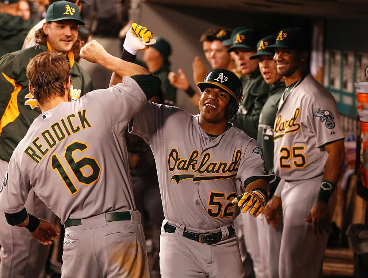 SEATTLE, WA - JUNE 21: Yoenis Cespedes #52 of the Oakland Athletics is congratulated by Josh Reddick #16 after hitting a two-run home run in the ninth inning against the Seattle Mariners at Safeco Field on June 21, 2013 in Seattle, Washington. (Photo by Otto Greule Jr/Getty Images)