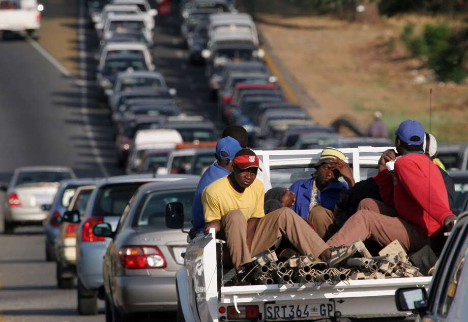 "No. 40 -- South Africa, $5.38  With low per capita incomes and moderate gas use, South Africans are second to none in the share of their paychecks that goes to fueling up. The situation in South Africa worsened over the quarter, with a 6.2 percent increase in the price of gasoline. Pump prices are determined on a monthly basis by the Central Energy Fund, a state-owned entity set up in 1997.  [Photo: Laborers sit in the back of a ""bakkie"" during rush-hour traffic in Johannesburg, South Africa.] Photo: DENIS FARRELL, AP"