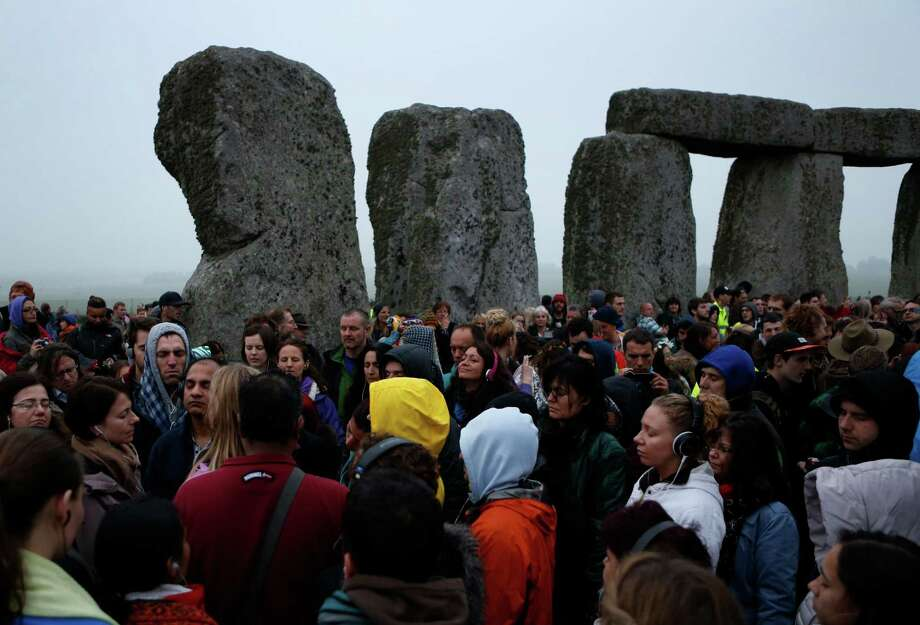 People meditate during the summer solstice shortly after 04.52 am at the prehistoric Stonehenge monument, near Salisbury, England, Friday, June 21, 2013. Following an annual all-night party, thousands of new agers and neo-pagans waited at the ancient stone circle Stonehenge for the sun to come up, but cloudy skies prevented them. They danced and whooped in delight marking the summer solstice, the longest day of the year. Photo: Lefteris Pitarakis, AP / AP