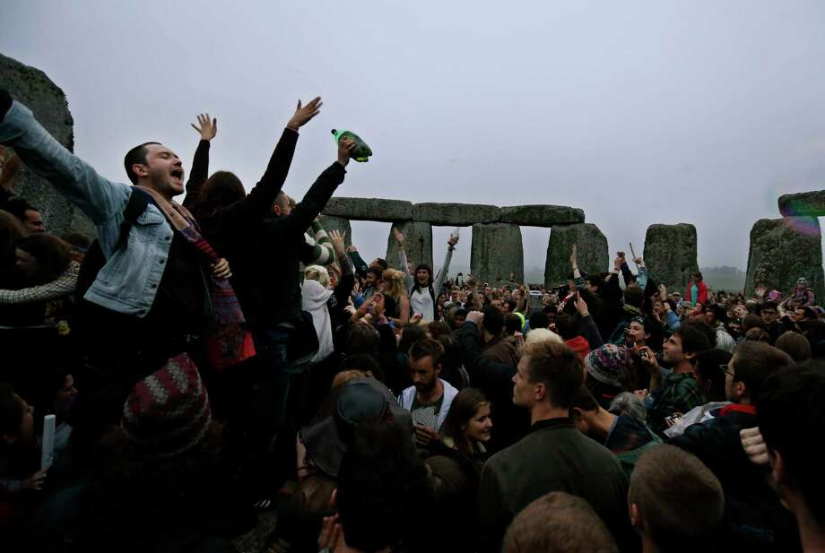 People dance and raise their hands in celebration during the summer solstice shortly after 04.52 am at the prehistoric Stonehenge monument, near Salisbury, England, Friday, June 21, 2013. Following an annual all-night party, thousands of new agers and neo-pagans waited at the ancient stone circle Stonehenge for the sun to come up, but cloudy skies prevented them. They danced and whooped in delight marking the summer solstice, the longest day of the year. Photo: Lefteris Pitarakis, AP / AP