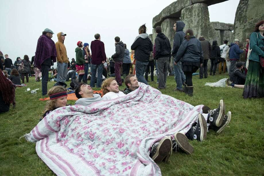 Revelllers lie under a blanket as they celebrate the pagan festival of 'Summer Solstice' at Stonehenge in Wiltshire in southern England, on June 21, 2013. The festival, which dates back thousands of years, celebrates the longest day of the year when the sun is at its maximum elevation. Modern druids and people gather at the landmark Stonehenge every year to see the sun rise on the first morning of summer.   AFP PHOTO / JUSTIN TALLISJUSTIN TALLIS/AFP/Getty Images Photo: JUSTIN TALLIS, AFP/Getty Images / AFP