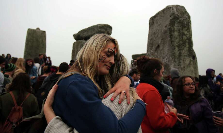 AMESBURY, ENGLAND - JUNE 21:  Revellers gather as druids, pagans and revellers celebrate the summer solstice at the megalithic monument of Stonehenge on June 21, 2013 near Amesbury, England. Despite cloudy skies, thousands of revellers gathered at the 5,000 year old stone circle in Wiltshire to see the sunrise on the Summer Solstice dawn. The solstice sunrise marks the longest day of the year in the Northern Hemisphere. Photo: Matt Cardy, Getty Images / 2013 Getty Images
