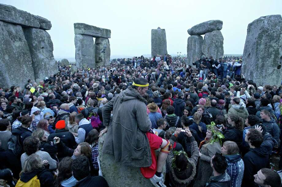 Revelllers celebrate the pagan festival of 'Summer Solstice' at Stonehenge in Wiltshire in southern England, on June 21, 2013. The festival, which dates back thousands of years, celebrates the longest day of the year when the sun is at its maximum elevation. Modern druids and people gather at the landmark Stonehenge every year to see the sun rise on the first morning of summer.   AFP PHOTO / JUSTIN TALLISJUSTIN TALLIS/AFP/Getty Images Photo: JUSTIN TALLIS, AFP/Getty Images / AFP