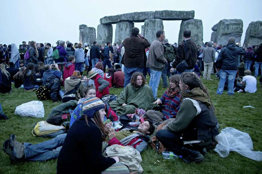 Revelllers gather to celebrate the pagan festival of 'Summer Solstice' at Stonehenge in Wiltshire in southern England, on June 21, 2013. The festival, which dates back thousands of years, celebrates the longest day of the year when the sun is at its maximum elevation. Modern druids and people gather at the landmark Stonehenge every year to see the sun rise on the first morning of summer.   AFP PHOTO / JUSTIN TALLISJUSTIN TALLIS/AFP/Getty Images Photo: JUSTIN TALLIS, AFP/Getty Images / AFP