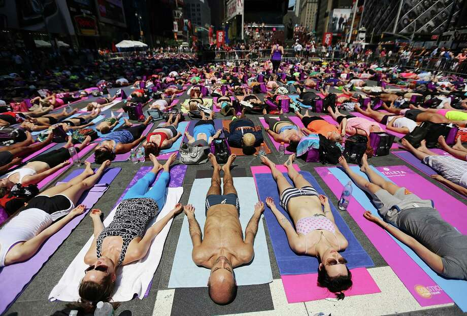 NEW YORK, NY - JUNE 21:  Simeone Scaramozzino (C) and other enthusiasts perform yoga in Times Square during an event marking the summer solstice on June 21, 2013 in New York City. Thousands of yogis will attend the free day-long event in Manhattan on the longest day of the year. Photo: Mario Tama, Getty Images / 2013 Getty Images
