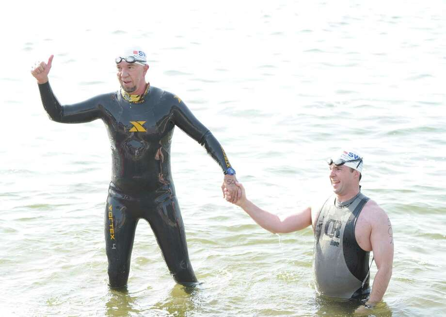 Herve Hamon, left, of Norwalk, and Donald McCrossen of Old Greenwich, were the first swimmers to finish during the Swim Across America event for the Greenwich-Stamford area at Cummings Point in Stamford, Saturday morning, June 22, 2013. Swim Across America, Inc., is an organization dedicated to raising money and awareness for cancer research, prevention and treatment, through swimming- related events. Photo: Bob Luckey / Greenwich Time