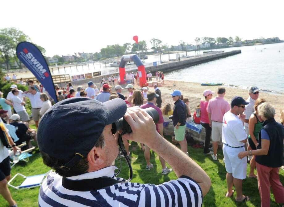 Dan Fass of Greenwich uses binoculars to look for his daughter, Sara Fass, who was swimming Long Island Sound as part of the Swim Across America event for the Greenwich-Stamford area at Cummings Point in Stamford, Saturday morning, June 22, 2013. Fass said his daughter was swimming to honor Gen Bosson of New York City who passed away from Cancer in August of 2012. Bosson was a chief Radiation Therapist at Greenwich Hospital. Swim Across America, Inc., is an organization dedicated to raising money and awareness for cancer research, prevention and treatment, through swimming- related events. Photo: Bob Luckey / Greenwich Time