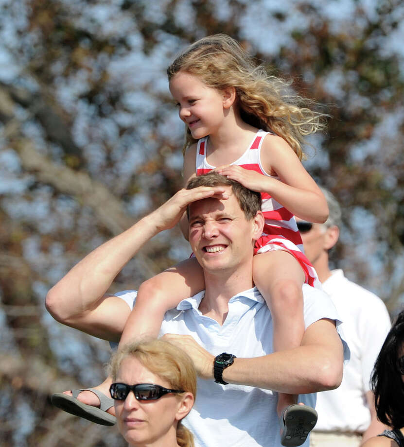 With his daughter Amelie, 5, on his shoulders, Martin Ayre of Greenwich, looks out toward Long Island Sound for his wife, Cecila, who was taking part in the Swim Across America event for the Greenwich-Stamford area at Cummings Point in Stamford, Saturday morning, June 22, 2013. Swim Across America, Inc., is an organization dedicated to raising money and awareness for cancer research, prevention and treatment, through swimming- related events. Photo: Bob Luckey / Greenwich Time