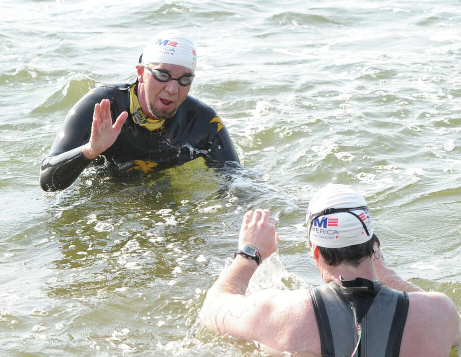 Herve Hamon, left, of Norwalk, high-fives Donald McCrossen of Old Greenwich, as the pair were the first swimmers to finish during the Swim Across America event for the Greenwich-Stamford area at Cummings Point in Stamford, Saturday morning, June 22, 2013. Swim Across America, Inc., is an organization dedicated to raising money and awareness for cancer research, prevention and treatment, through swimming- related events. Photo: Bob Luckey / Greenwich Time