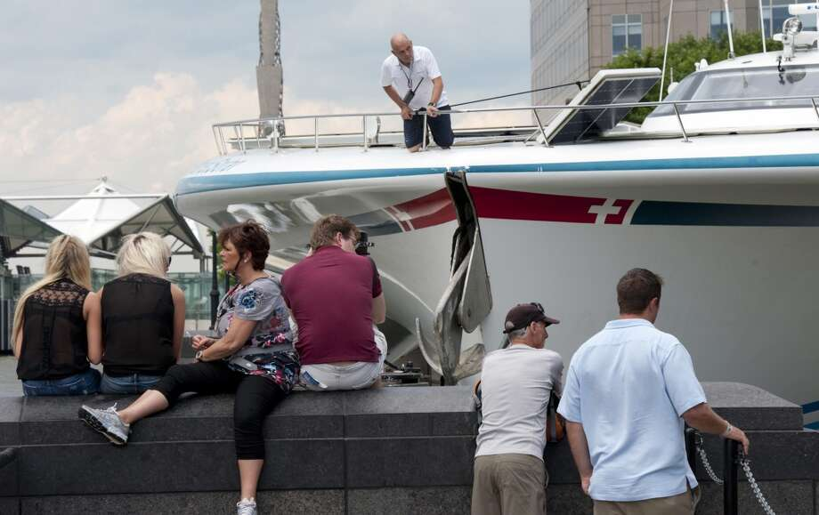 Spectators watch as the worlds largest solar boat, Switzerlands MS Tûranor PlanetSolar, arrives at North Cove marina June 17, 2013 in New York. The DeepWater Expedition, with scientists on board from the University of Geneva, is collecting climate change related data along the Gulf Stream. AFP PHOTO/Don EmmertDON EMMERT/AFP/Getty Images Photo: DON EMMERT, AFP/Getty Images