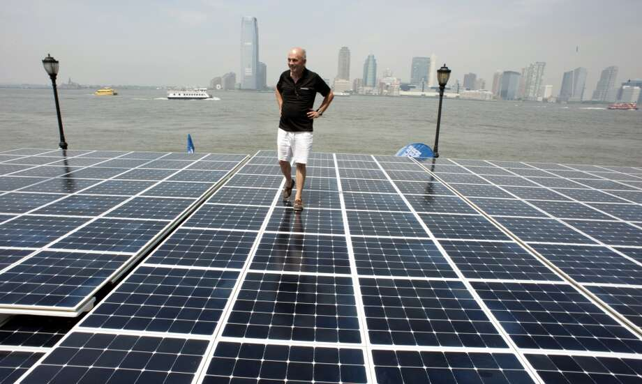 Gerard dAboville, captain of the worlds largest solar boat, Switzerlands MS Turanor PlanetSolar, stands on the boat's solar panels on June 18, 2013 at North Cove Marina in New York. The solar-powered boat runs exclusively on energy from the sun and eliminates the need for fueled electricity, allowing researchers to collect uncontaminated data along the Gulf Stream with high-tech instruments that track changes in ocean currents and climate. Solar panels cover more than 5,554 square feet (516 square meters) of the ships surface.  AFP PHOTO/Don EmmertDON EMMERT/AFP/Getty Images Photo: DON EMMERT, AFP/Getty Images