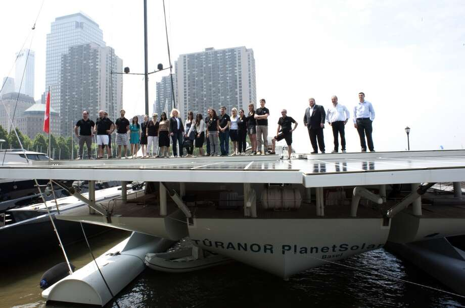 Scientists and crew aboard the worlds largest solar boat, Switzerlands MS Turanor PlanetSolar, pose for a photo on June 18, 2013 at North Cove Marina in New York. PlanetSolar is in New York City as part of its DeepWater Expedition 2013 tour with scientists on board from the University of Geneva. The solar-powered boat runs exclusively on energy from the sun and eliminates the need for fueled electricity, allowing researchers to collect uncontaminated data along the Gulf Stream with high-tech instruments that track changes in ocean currents and climate. Solar panels cover more than 5,554 square feet (516 square meters) of the ships surface.    AFP PHOTO/Don EmmertDON EMMERT/AFP/Getty Images Photo: DON EMMERT, AFP/Getty Images