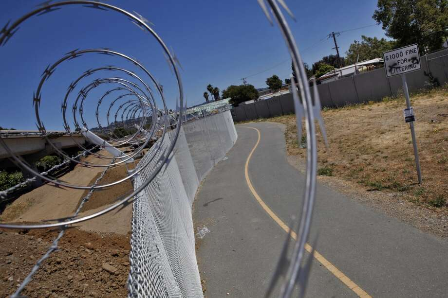 Richmond Vice Mayor Corky Boozé is facing a lawsuit by the city council for failing to comply with blight ordinances, but he says that his property is not visible from the public thoroughfare and the razor wire put up near BART tracks is more unsightly than his property behind the fence on the right. He shows his commercial property on Wednesday, June 19, 2013, in Richmond, Calif.