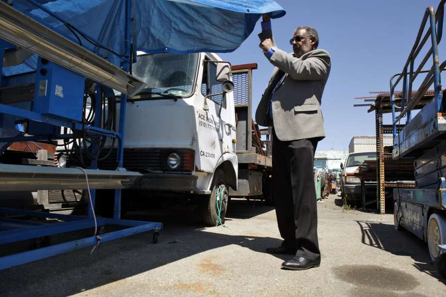 Richmond Vice Mayor Corky Boozé looks under a tarp at a automotive paint curing lights stored on his commercial property on Wednesday, June 19, 2013, in Richmond, Calif.  Boozé is facing a lawsuit by the city council for failing to comply with blight ordinances.