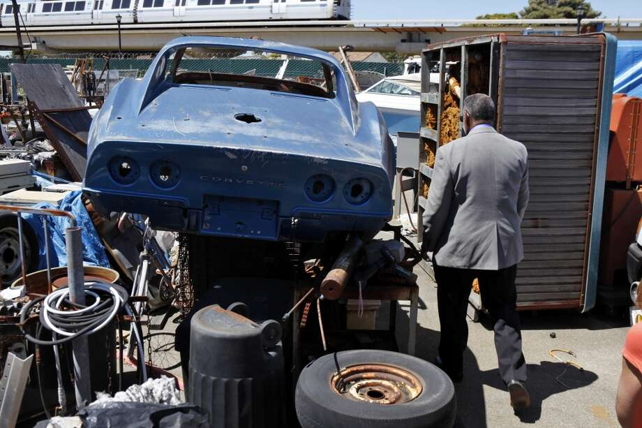 Richmond Vice Mayor Corky Boozé walks past a corvette his is intending to restore on his commercial property on Wednesday, June 19, 2013, in Richmond, Calif. Boozé is facing a lawsuit by the city council for failing to comply with blight ordinances.