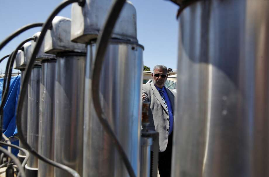 Richmond Vice Mayor Corky Boozé stands behind a paint mixer on his commercial property on Wednesday, June 19, 2013, in Richmond, Calif. . Boozé is facing a lawsuit by the city council for failing to comply with blight ordinances.