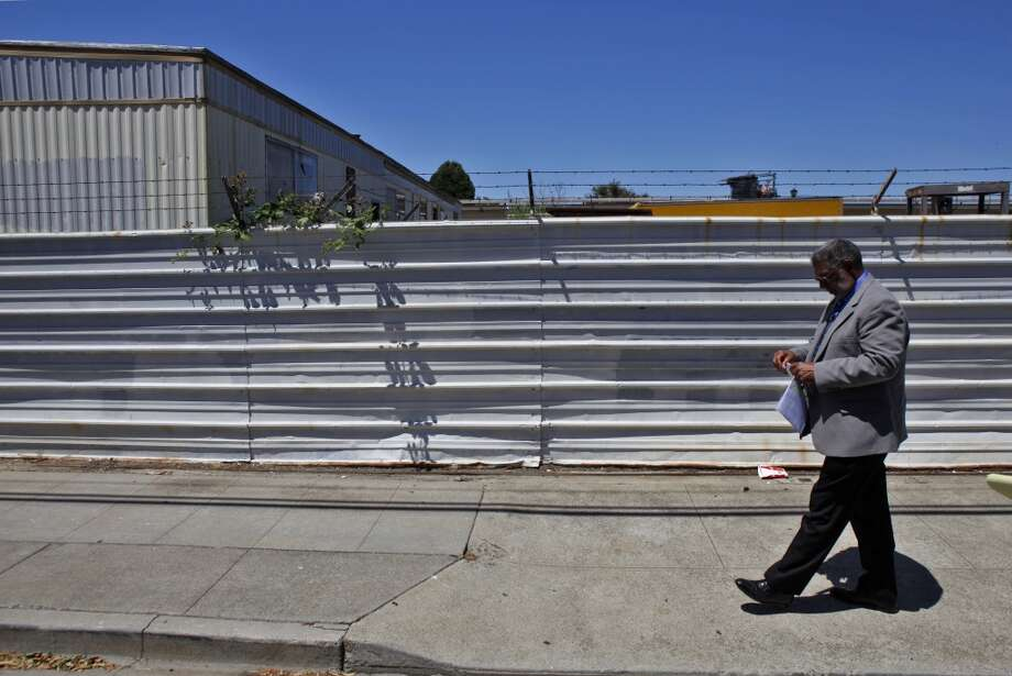 Richmond Vice Mayor Corky Boozé walks along the fence of his commercial property on Wednesday, June 19, 2013, in Richmond, Calif.  Boozé is facing a lawsuit by the city council for failing to comply with blight ordinances. He claims that the charges are politically motivated, and that the items on the property are not visible from the street.