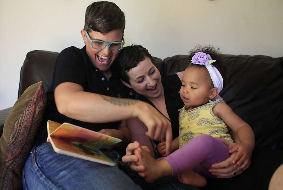 Marlene White (left) and Elana Metz of Oakland read a story to their daughter, Nia. Photo: Mike Kepka, The Chronicle