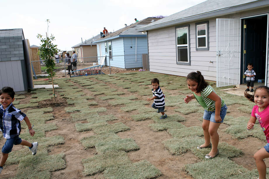 Habitat for Humanity of San Antonio works on houses as children play around in the back yard of the newly dedicated house of  Norman and Martha Vazquez on Emmaus Trail after house dedication ceremonies for nine families on June 22, 2013. Photo: Cynthia Esparza, For San Antonio Express-News / For San Antonio Express-News