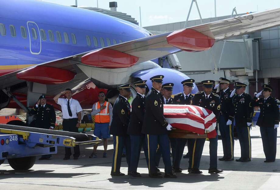 The flag-draped casket of Lt. Col. Todd Clark arrives at San Antonio International Airport aboard a Southwest Airlines jet on Wednesday, June 19, 2013. He was an instructor in the 10th Mountain Division in Afghanistan and was killed on Saturday by an Afghan National Army soldier during an argument. He already had a Purple Heart for injuries suffered in a roadside bomb attack during a previous deployment. Photo: Billy Calzada / San Antonio Express-News