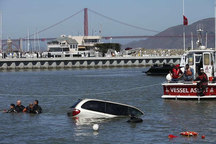 A gold mini van drove into the Marina at Marina Green yesterday evening and was extracted from the water this morning, Saturday June 22, 2013 in San Francisco, Calif. A rescue team removes the body from the water using a body bag and a stretcher before towing the van out of the water. The San Francisco police department, fire department and vessel assist all contributed to the effort to tow the van out of the bay. Photo: Katie Meek, The Chronicle