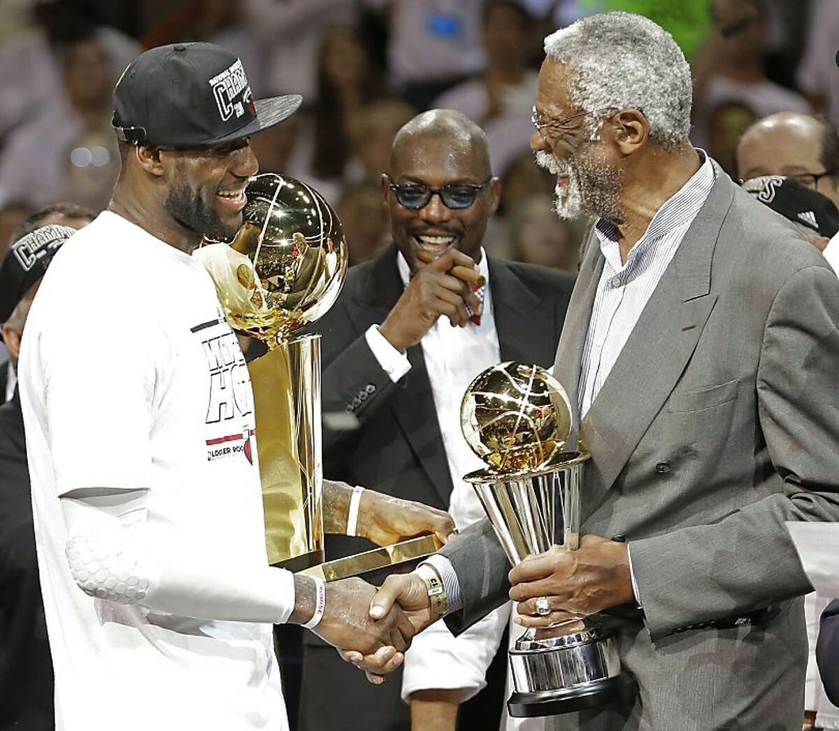 The Miami Heat's LeBron James, left, holding the Larry O'Brien NBA Championship Trophy is given the Bill Russell NBA Finals Most Valuable Player Award, by Former NBA player Bill Russell after Game 7 of the NBA basketball championship against the San Antonio Spurs, Friday, June 21, 2013, in Miami. The Miami Heat defeated the San Antonio Spurs 95-88 to win their second straight NBA championship. (AP Photo/Lynne Sladky