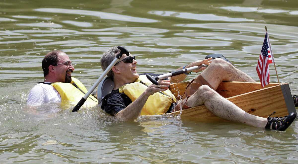 Mark Danna, left, and Mark Smith, right, try to stay afloat during the Anything That Floats competition at Sesquicentennial Park Saturday, June 22, 2013, in Houston. Organized by rdAgents, a young professionals network affiliated with the Rice Design Alliance, the participants have a few hours to build a device to float a short distance across Buffalo Bayou with discarded building materials. The boats must be able to support two passengers.