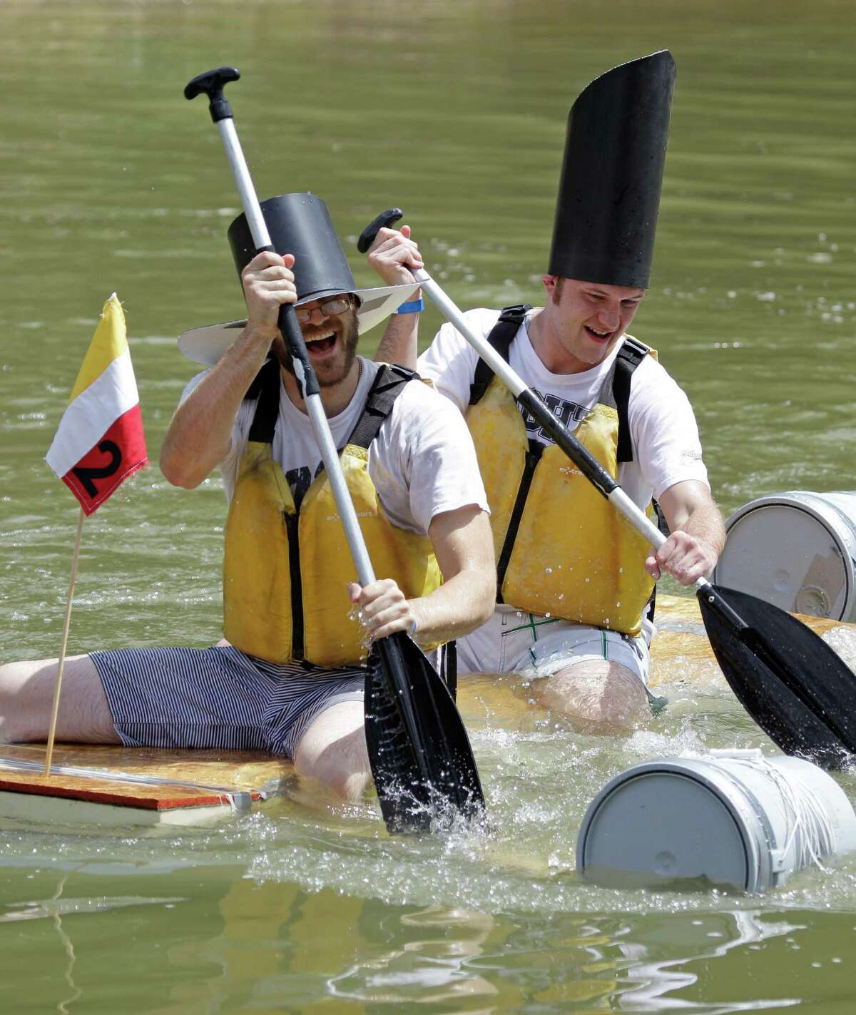 Trevor Best, left, and Jason Slater, right, work to paddle across the bayou during the Anything That Floats competition at Sesquicentennial Park Saturday, June 22, 2013, in Houston. Organized by rdAgents, a young professionals network affiliated with the Rice Design Alliance, the participants have a few hours to build a device to float a short distance across Buffalo Bayou with discarded building materials. The boats must be able to support two passengers.