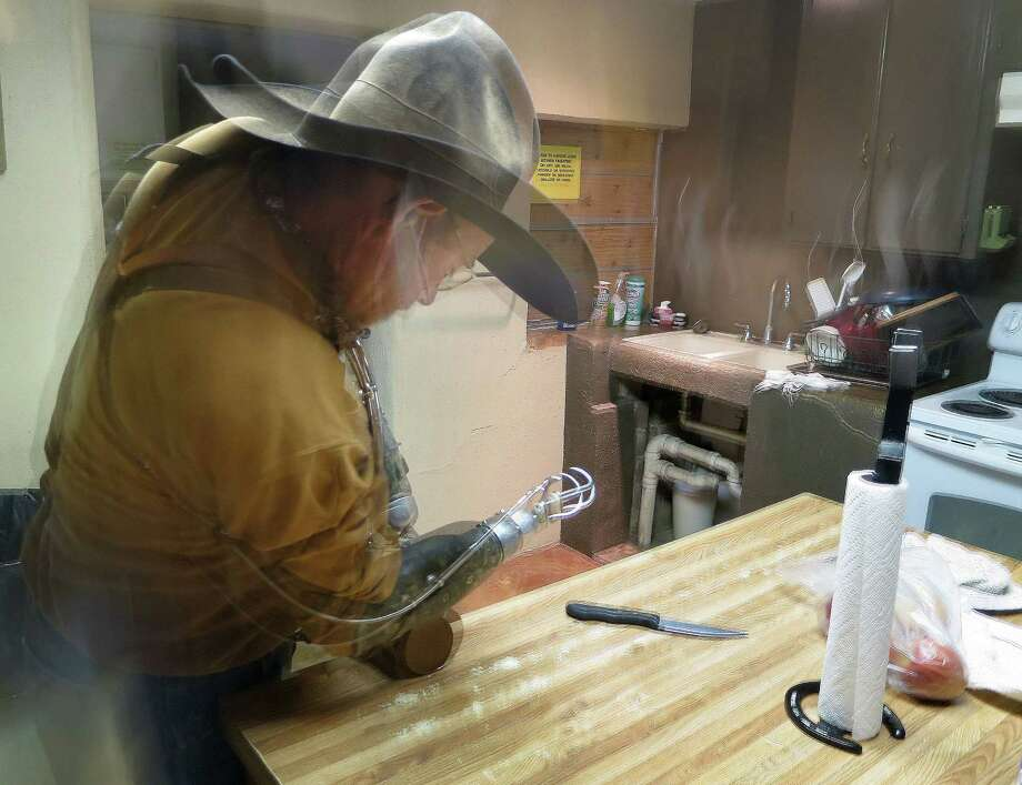 Charley Bowers, tries to open a jar of peanut butter in his  kitchen in Knickerbocker, Texas, 15 miles south of San Angelo.   Bowers, 56, is a cowboy, hunting guide, camp cook, a welder, a mechanic – a jack-of-all-rural trades, in other words – despite having lost both hands four years ago in a horrific electrical accident. Charley was in a bucket lift working on his mother-in-law's barn when a charge from a nearby power line coursed through his body. Most the photos were taken at the Adobe Lodge Hunting Camp, near Knickerbocker, owned by Charley's friend Skipper Duncan. Photo: Joe Holley, Houston Chronicle / Houston Chronicle