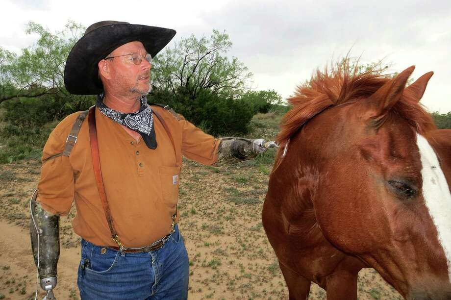Charley Bowers, pets a horse on his land in Knickerbocker, Texas, 15 miles south of San Angelo.   Bowers, 56, is a cowboy, hunting guide, camp cook, a welder, a mechanic – a jack-of-all-rural trades, in other words – despite having lost both hands four years ago in a horrific electrical accident. Charley was in a bucket lift working on his mother-in-law's barn when a charge from a nearby power line coursed through his body. Most the photos were taken at the Adobe Lodge Hunting Camp, near Knickerbocker, owned by Charley's friend Skipper Duncan. Photo: Joe Holley, Houston Chronicle / Houston Chronicle