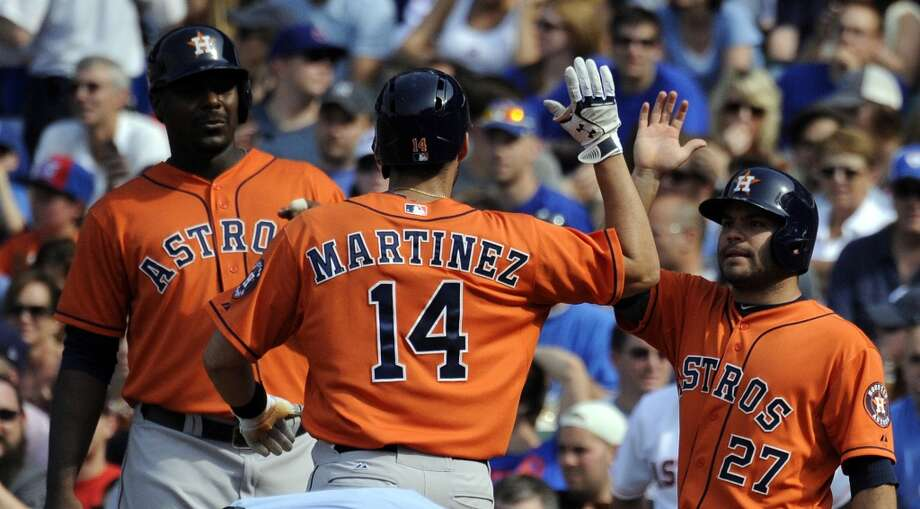 J.D. Martinez celebrates with teammates Jose Altuve, and Chris Carter after hitting a three-run home run.