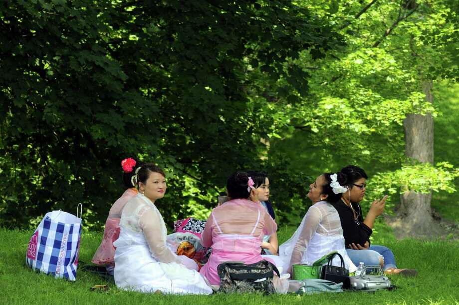 A group of ladies sit in the shade during the 7th Annual World Refugee Day picnic in Washington Park  on Saturday June 22, 2013 in Albany, N.Y. (Michael P. Farrell/Times Union) Photo: Michael P. Farrell