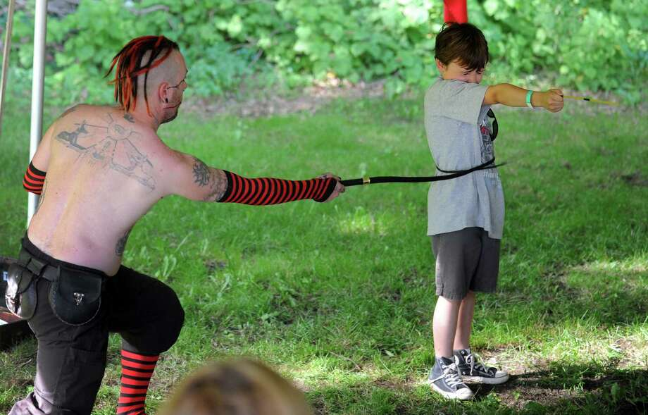Wyck Aj performs during The Midsummer Fantasy Renaissance Faire Saturday, June 22, 2013 at Warsaw Park  in Ansonia, Conn.  Seven-year-old Wyatt Corey, of Seymour, holds out a spaghetti straw for Wyck to split with his whip during the show. Photo: Autumn Driscoll / Connecticut Post
