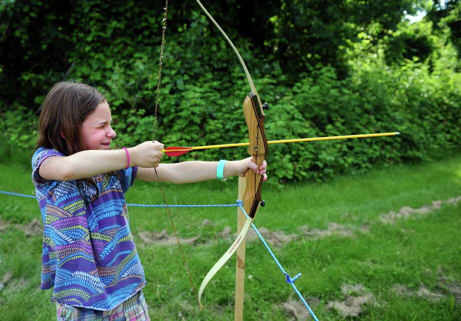 Seven-year-old Sara Prodan, of Seymour, aims her arrow at the target during the Midsummer Fantasy Renaissance Faire Saturday, June 22, 2013 at Warsaw Park  in Ansonia, Conn. Photo: Autumn Driscoll / Connecticut Post