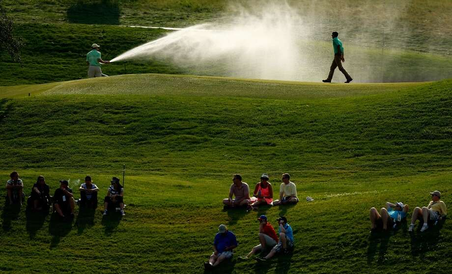 CROMWELL, CT- JUNE 22: A groundskeeper waters the 2nd green while fans watch the action on the 17th fairway below during the third round of the 2013 Travelers Championship at TPC River Highlands on June 22, 2012 in Cromwell, Connecticut.  (Photo by Jared Wickerham/Getty Images)