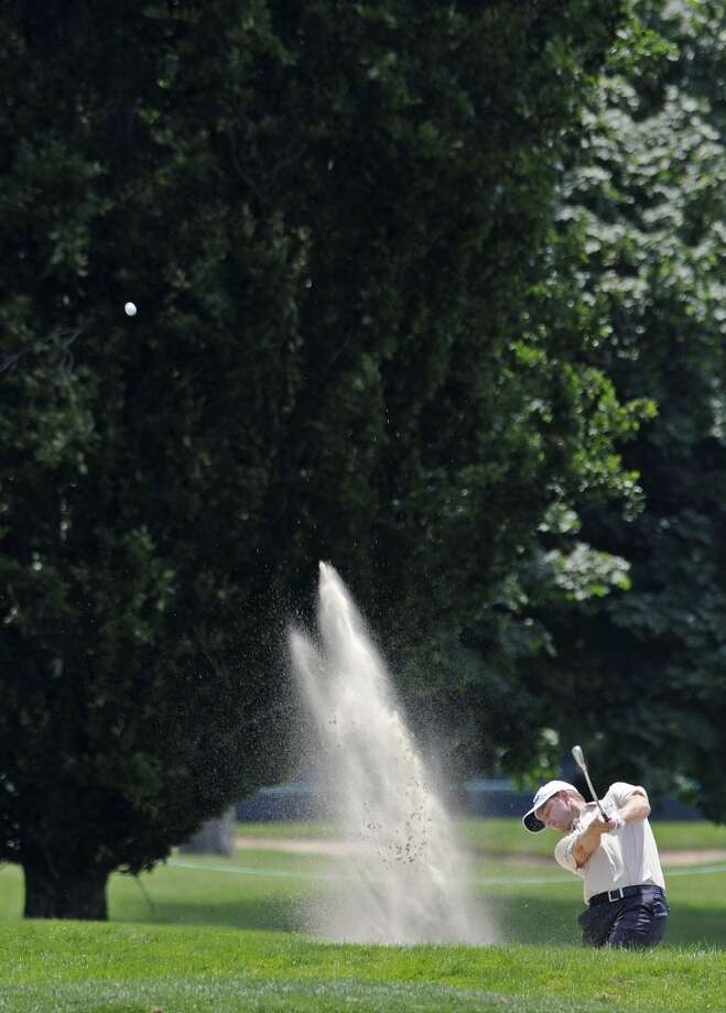 John Merrick hits out of a bunker on the seventh hole during the third round of the Travelers Championship golf tournament in Cromwell, Conn., Saturday, June 22, 2013. (AP Photo/Fred Beckham)