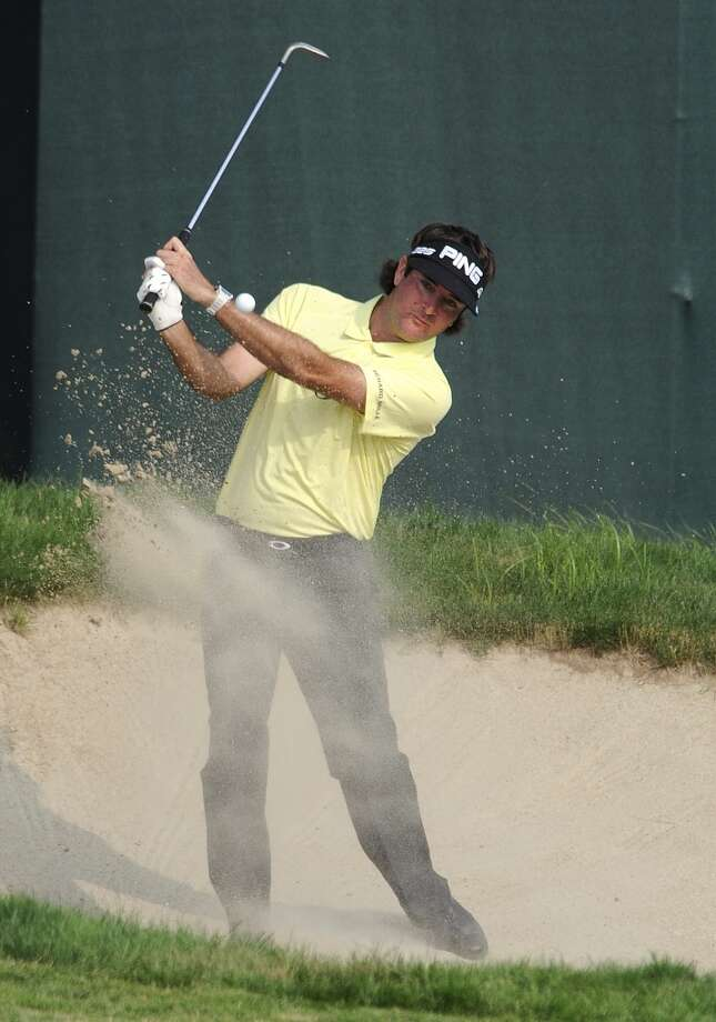 Bubba Watson chips out of a bunker on the 17th hole during the third round of the Travelers Championship golf tournament in Cromwell, Conn., Saturday, June 22, 2013. Watson bogeyed the hole and shot an even par 70 to remain 10-under par for the tournament, in a three-way tie for the lead. (AP Photo/Fred Beckham)