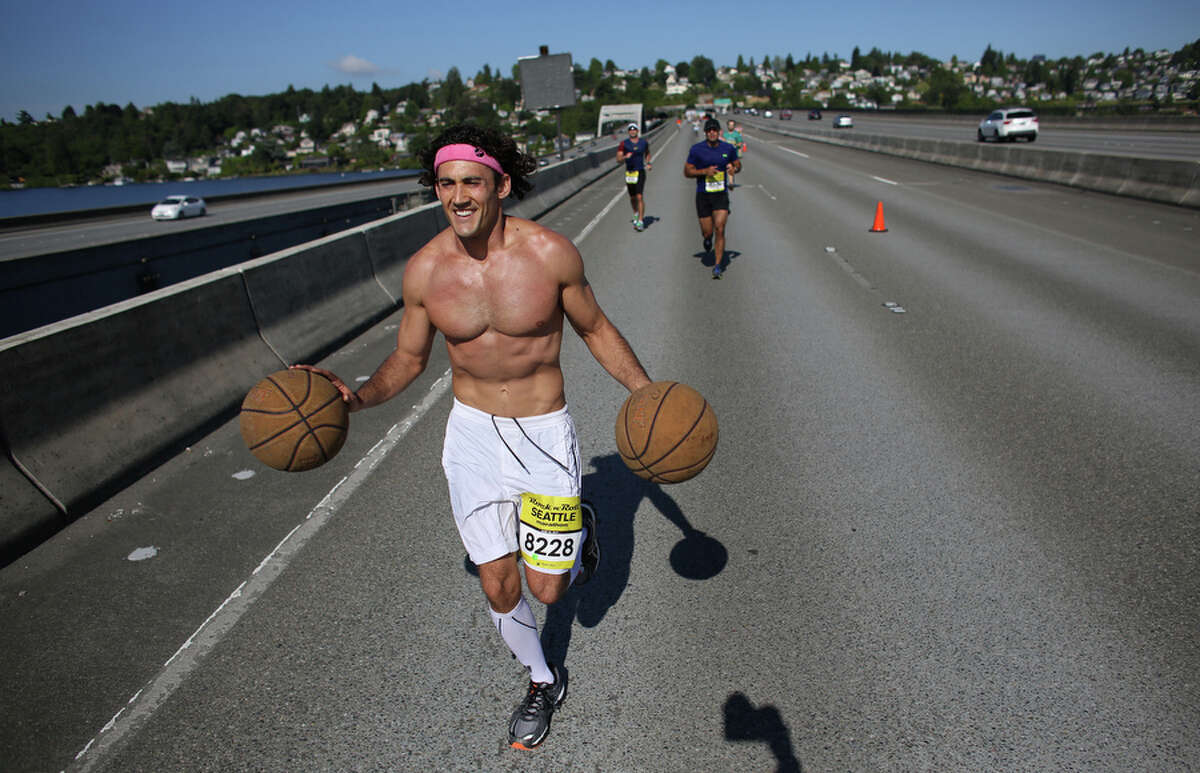 Darren Weismann, also know as Doctor Dribble, attempts to break a Guinness World Record for fastest marathon while dribbling two basketballs during the annual Rock 'n' Roll Seattle Marathon on Saturday, June 22, 2013. More than 20,000 participants started the 26.2 mile marathon course and 13.1 1/2 marathon course.