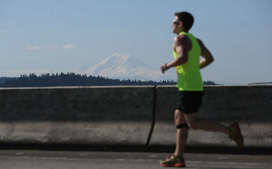 Mt. Rainier is shown as runner makes his way along Interstate 90 during the annual Rock 'n' Roll Seattle Marathon. Photo: JOSHUA TRUJILLO, SEATTLEPI.COM / SEATTLEPI.COM