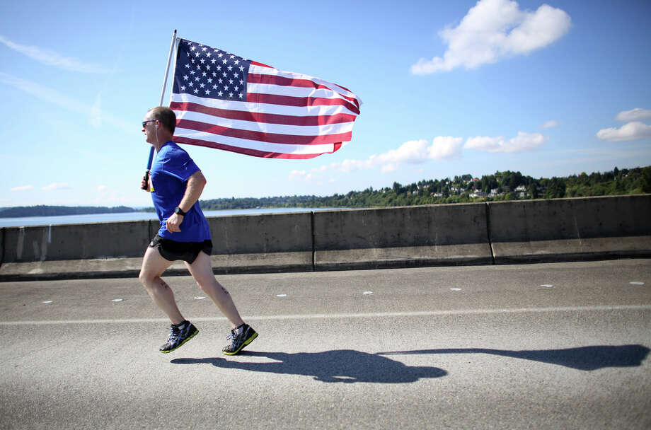 Bill Beadle carries the Stars and Stripes to honor a fallen solider. Photo: JOSHUA TRUJILLO, SEATTLEPI.COM / SEATTLEPI.COM