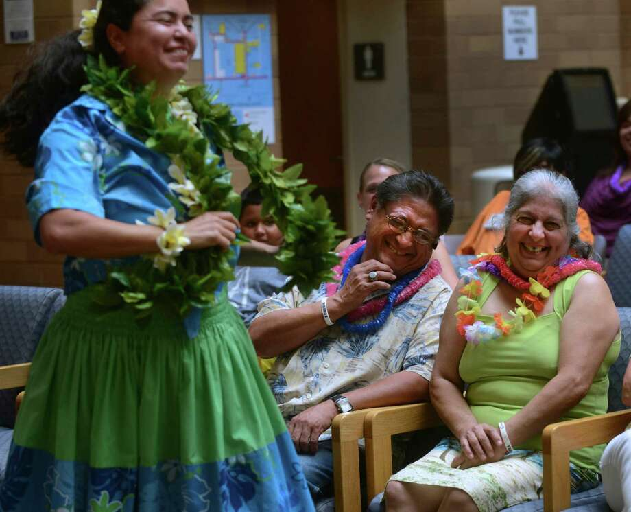 Soila Moreno, right, and her husband, Domingo, laugh as they are entertained by the Hawaiian cultural group Hula Halau Ohana Elikapeka during the annual Cancer Survivors Day Celebration at San Antonio Military Medical Center on Saturday, June 22, 2013. Soila Moreno has been treated for colon cancer. Photo: Billy Calzada, San Antonio Express-News / San Antonio Express-News