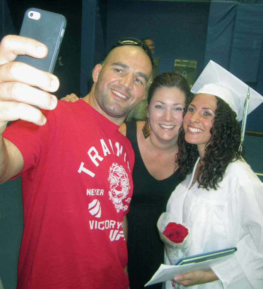 New graduate Taylor Daniels gladly poses for a photo with her uncle and aunt, Glover Teixeira and Ingrid Peterson-Teixeira, moments after Saturday's New Milford High School graduation ceremony at the O'Neill Center on the campus of Western Connecticut State University in Danbury.  June 22, 2013 Photo: Norm Cummings