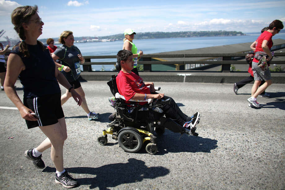 Terry Hoefer, center, rolls along the course on the Alaskan Way Viaduct alongside his mom, Vickie, left, during the annual Rock 'n' Roll Seattle Marathon. Marathon organizers changed the course of the race to accommodate Terry and his wish to compete. You can read a story about that here. Photo: JOSHUA TRUJILLO, SEATTLEPI.COM / SEATTLEPI.COM