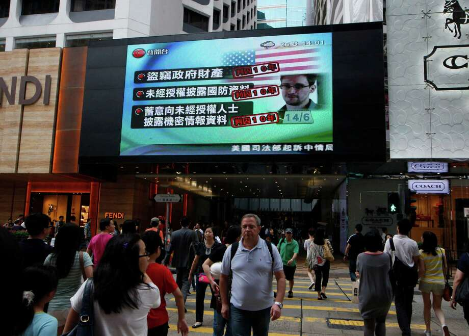A TV screen shows a news report of Edward Snowden, a former CIA employee who leaked top-secret documents about sweeping U.S. surveillance programs, at a shopping mall in Hong Kong Saturday, June 22, 2013. Hong Kong was silent Saturday on whether the former National Security Agency contractor should be extradited to the United States now that he has been charged with espionage, but some legislators said the decision should be up to the Chinese government. (AP Photo/Kin Cheung) Photo: Kin Cheung