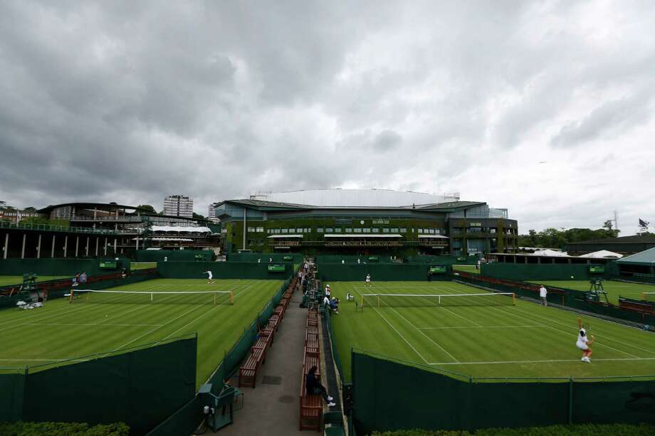 Under overcast skies, competitors practice on the grass courts at Wimbledon All England Lawn Tennis and Croquet Club in London, Saturday, June 22, 2013. The Wimbledon Championships start Monday June 24. (AP Photo/Sang Tan) Photo: Sang Tan
