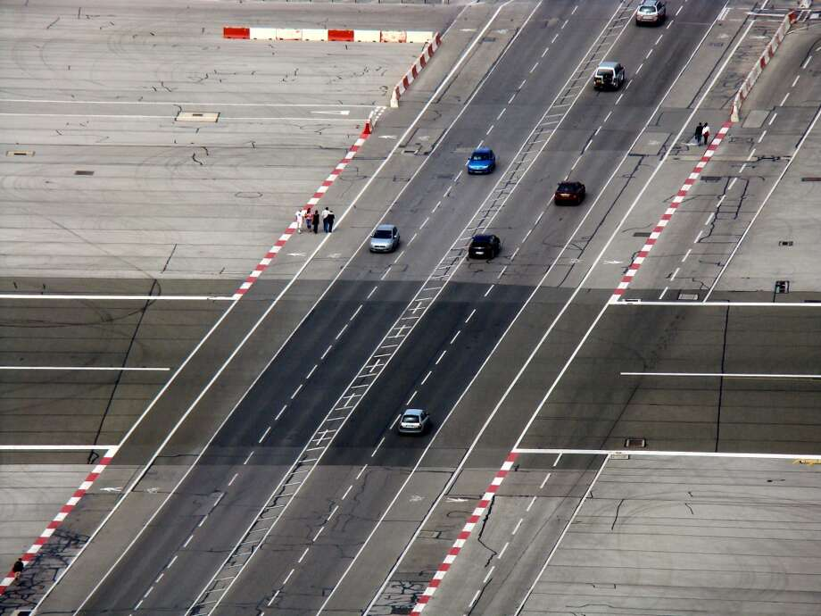 """Gibraltar Airport (Gibraltar)  """"The cross traffic runway""""  The primary runway at Gibraltar doubles as the city's main roadway. That's right, car traffic moves in a perpendicular path across the tarmac. When a plane approaches, railroad-like gates drop to keep cars clear. But while Gibraltar is probably the busiest airport on this list, it has miraculously never had a major accident. Photo: Mark Jansen / Kpmarek.com, Getty Images / Flickr RF"""