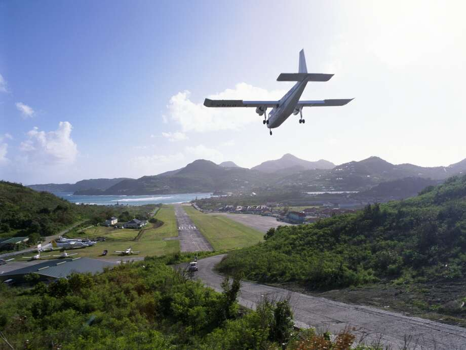 """Gustaf III Airport (French Caribbean) """"The traffic flyover""""  Nicknamed St. Barth's (serving the island of Saint Barthélemy), it's an airport without room for a full runway. The approach corridor actually passes over a well used public road—and the runway itself ends on the other side in the ocean. Photo: Stewart Cohen, Getty Images"""
