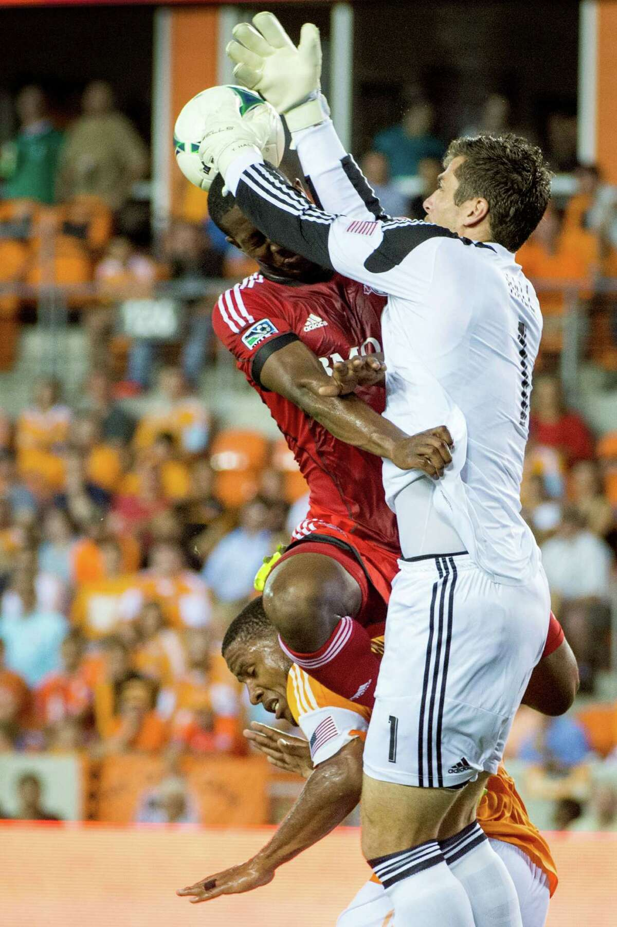 Dynamo 0, Toronto 0 Houston Dynamo goalkeeper Tally Hall knocks the ball away from Toronto FC defender Doneil Henry as they collide during the first half on Saturday, June 22, 2013, at BBVA Compass Stadium in Houston.